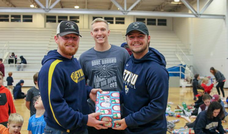Three male student-athletes show the OCC boxes they put together