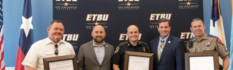 ETBU President J. Blair Blackburn and Vice President for Enrollment and Administrative Affairs Kevin Caffey present Harrison County Sheriff Tom McCool, Marshall Police Department Chief Cliff Carruth, and Texas Department of Public Safety Corporal Kevin Arnold during the annual Law Enforcement Appreciation Luncheon on May 14.